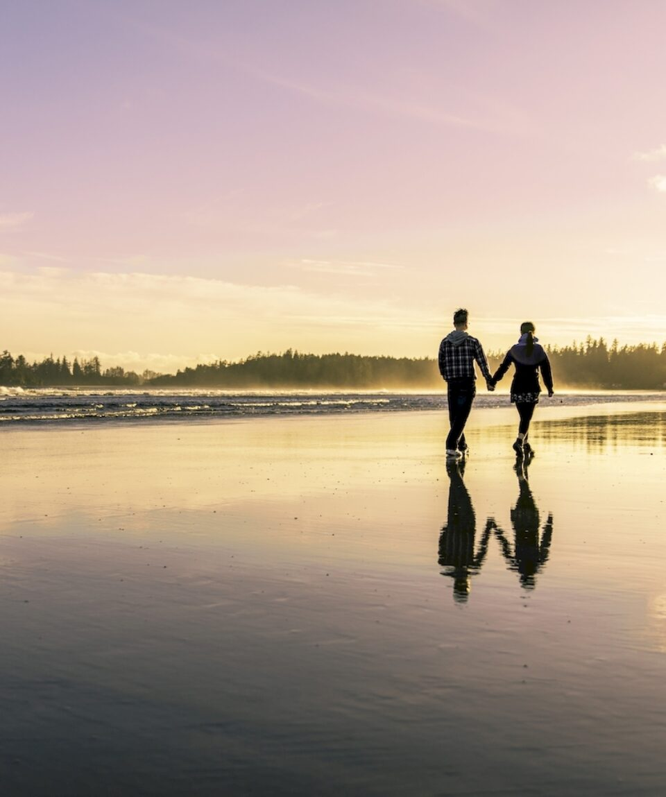 Couple going for a walk as the sun sets at Long Beach in Tofino during the summer