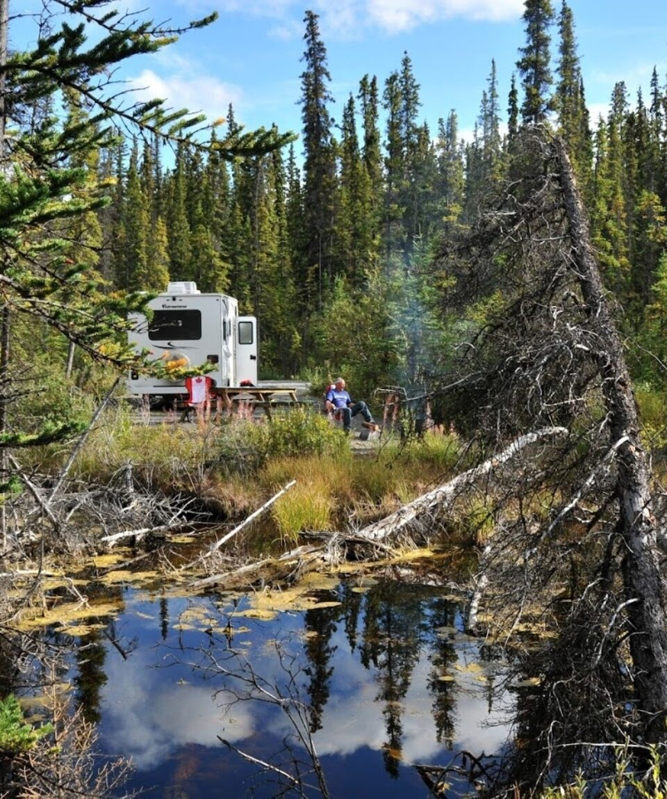 RV parked beside pond