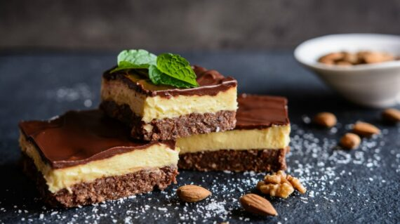 Nanaimo bars - traditional Canadian dessert with wafer crumbs, almond, walnut and cocoa layer, vanilla custard filling and choco